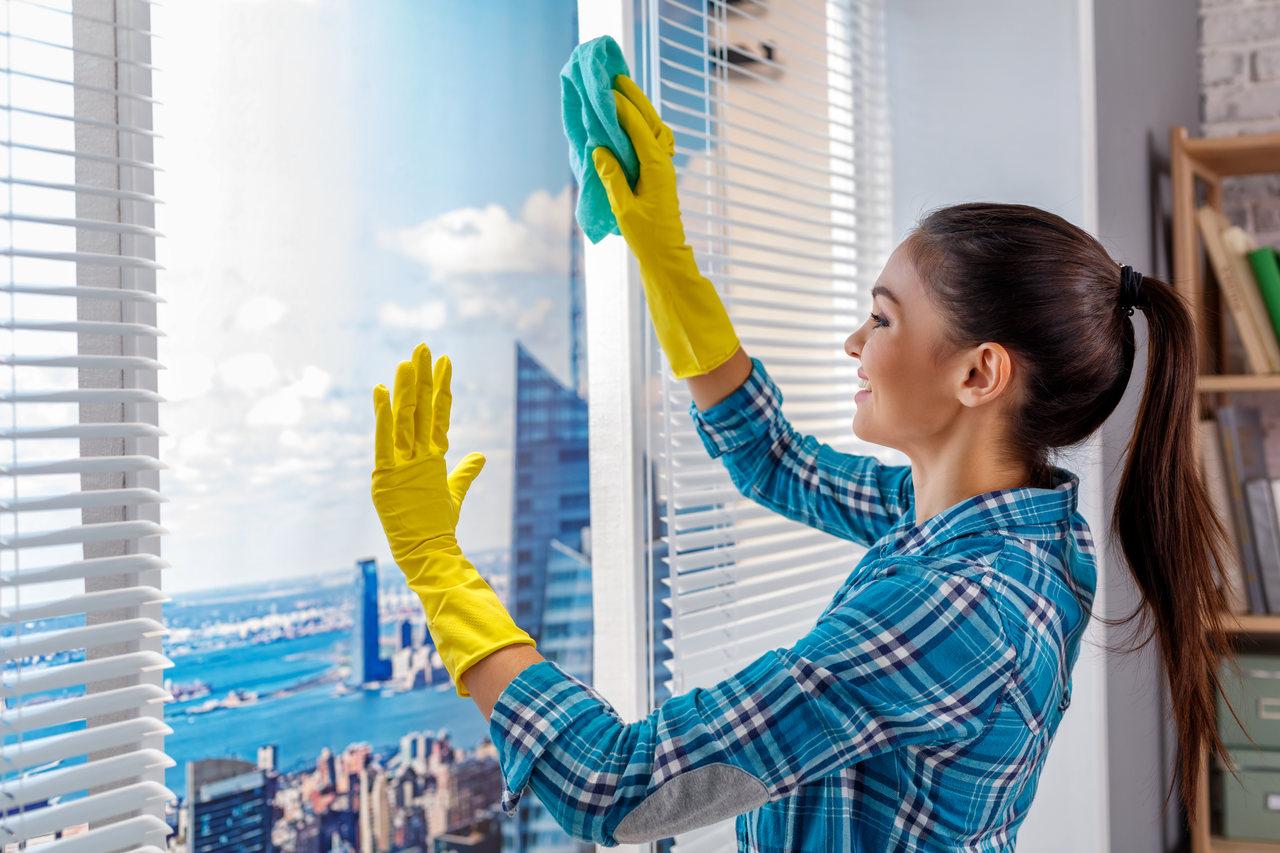 Kobieta w niebieskiej koszuli w kratę i żółtych rękawiczkach myje okna w domu